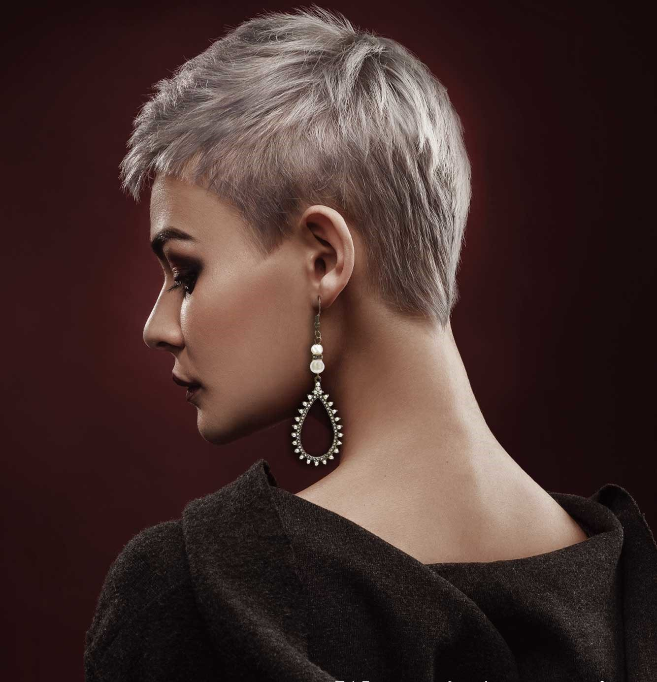White Woman wearing classy earrings in a black top on burgundy background. Dlaen's Jewelry p